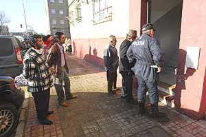 Vecinos y policía en el portal de Santiago del Valle. (Foto: Antonio Luis Delgado)