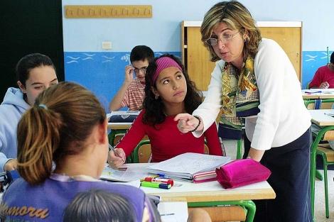 Una profesora conversa con sus alumnos en un colegio. | Carlos García.
