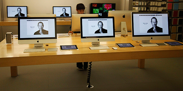 Un nio observa un ordenador con la imagen de Steve Jobs en una tienda Apple de California. | Reuters