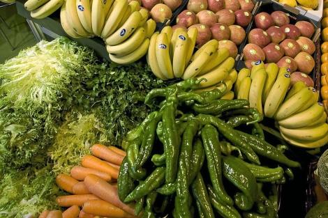 Plátanos, zanahorias y pimientos en un puesto de frutas y verduras. | E. M.