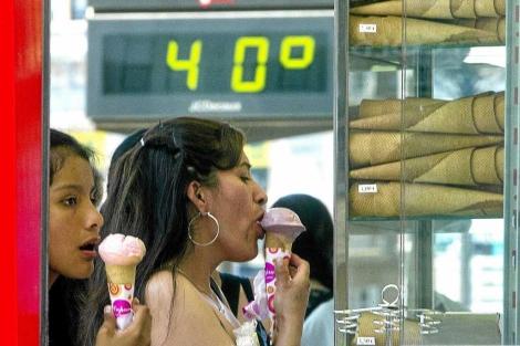 Dos chicas con un helado junto a un termómetro que marca 40 grados en Bilbao. | I. Andrés