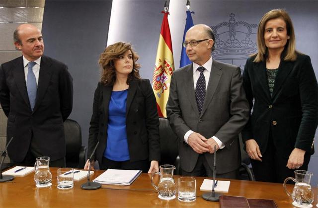 De izquierda de derecha, el ministro de Economía, Luis de Guindos, la portavoz Soraya Sáenz de Santamaría, el titular de Hacienda, Cristóbal Montoro, y la ministra de Trabajo, Fátima Báñez, tras la rueda de prensa. | Efe