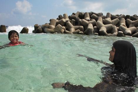 Una mujer con hiyab se baña en el mar en Male.