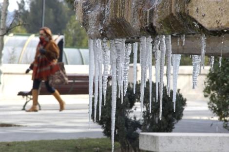 Una señora camina ante una fuente con estalactitas de hielo en Teruel. | Efe
