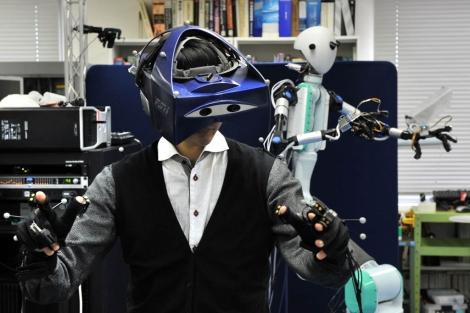 El robot y la persona que lo maneja a distancia con un casco de realidad virtual.   AFP