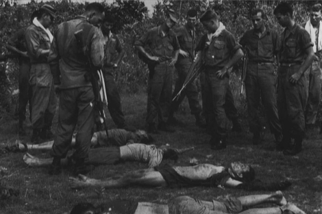 Varios 'marines' observan cadáveres de vietcongs durante la Guerra de Vietnam. | E. M.