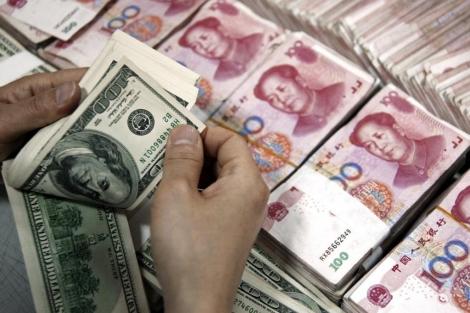 Un hombre cuenta dólares y yuanes. | Stringer Shanghai