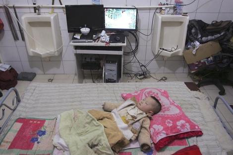 El bebé de Zeng Lijun duerme junto a los urinarios en su hogar. | Reuters