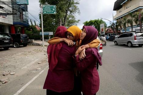 Tres mujeres se consuelan tras el terremoto en Aceh.   Afp