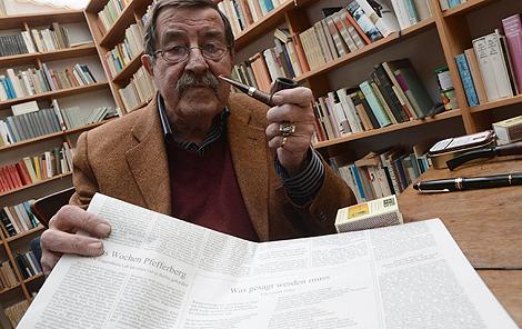 Günter Grass posa con un ejemplar del diario que publicó su poema. | Efe