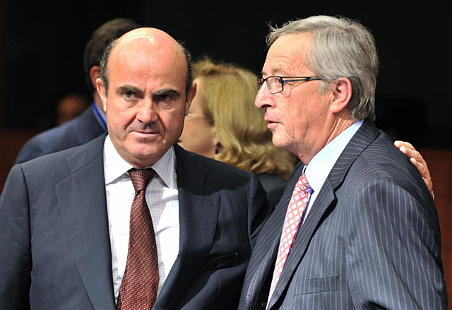 Luis de Guindos (izq.), junto al presidente del Eurogrupo, Jean-Claude Juncker. | Afp