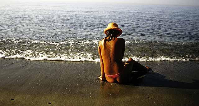 Una mujer se relaja en una playa. | El Mundo