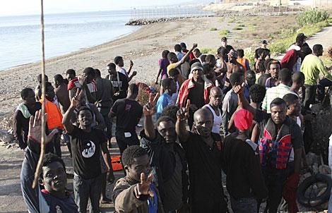 Algunos de los 91 inmigrantes de Ceuta tras alcanzar la playa. | Reduan / Efe