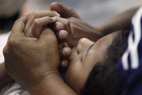 Un padre sujeta las manos de su hijo antes de la intervención.| Reuters