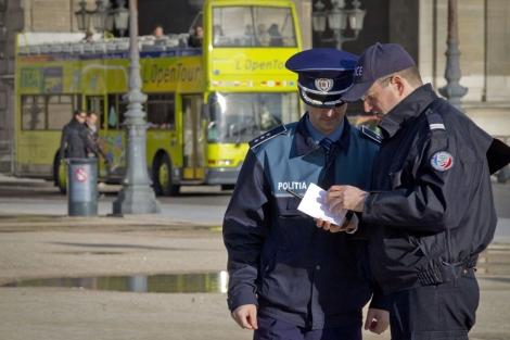 Un policía fránces muestra un mapa de París a un policía rumano. | AFP