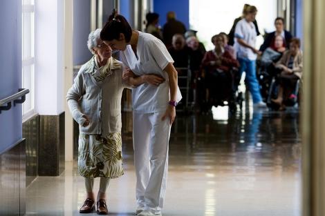 Una enfermera acompaña a una anciana por los pasillos del hospital. | Iñaki Andrés