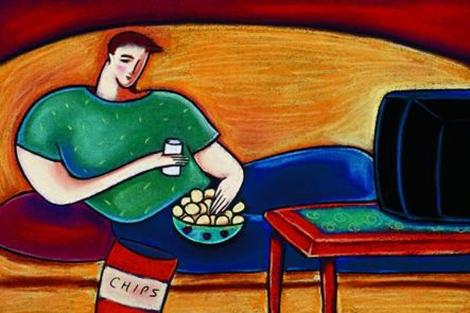 Un joven con exceso de peso, tumbado ante el televisor, mientras come patatas. | El Mundo