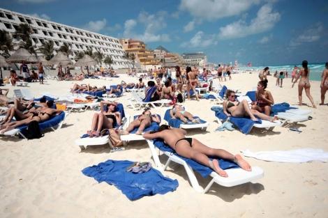 Jóvenes tomando el sol en una playa de la ciudad mexicana de Cancún. | Efe