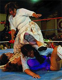 """La """"cholita"""" Carmen Rosa –de pie y sobre su compañera, Julia, """"la Paceña""""– controla con sus piernas a sus dos rivales """"occidentalizadas"""" durante una dura lucha de dos contra dos."""